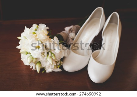 Bridal accessories: white shoes and  bouquet - stock photo