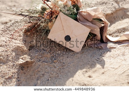 bridal bouquet and a letter in the sand