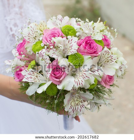 Bridal bouquet. Beautiful bouquet in hand of bride - stock photo