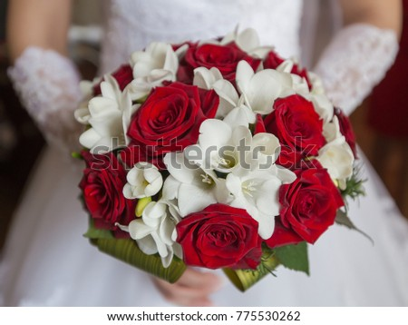 Bridal bouquet. Beautiful bridal bouquet from white and red flowers in hands of bride