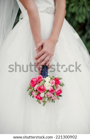Bridal bouquet from white and pink roses in the bride's hands