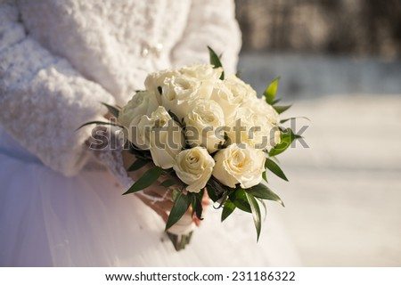 Bridal bouquet in hands in the winter. - stock photo