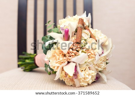 bridal bouquet of beige color on a chair with cinnamon - stock photo