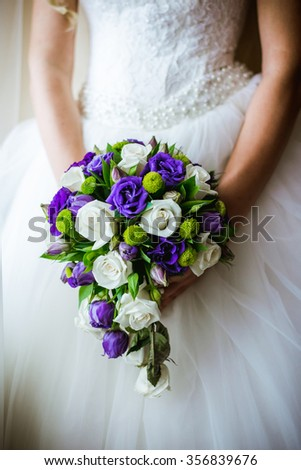 bridal bouquet of white and purple flowers, in the hands of the bride