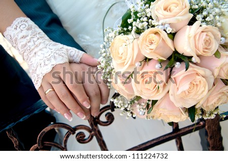 Bridal bouquet of white roses and hands of newlywed - stock photo