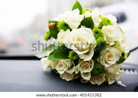 Bridal bouquet of white roses next to car windshield on the dashboard. Traffic jam on background