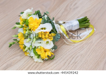 Bridal bouquet of yellow freesia and white eustoma and chrysanthemum . wedding style, thematic ideas .Background.  White and green flowers. - stock photo