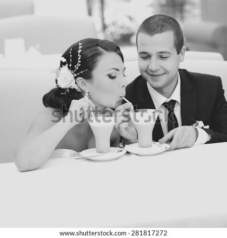 Bridal couple drinking cappuccino in summer cafe. Wedding portrait of beautiful newlyweds.