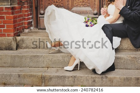 bridal couple sitting on stairs - stock photo