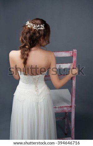 Bridal fashion. Brunette bride with pearl headpiece and white wedding gown view from the back. - stock photo