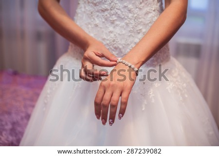 Bridal preparation, bride putting on jewelry, focus on bracelet. - stock photo