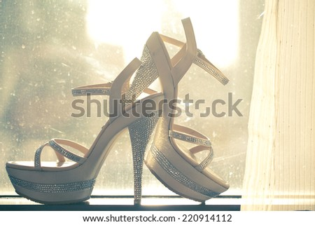 Bridal shoes at the window with sunset,vintage style photo - stock photo