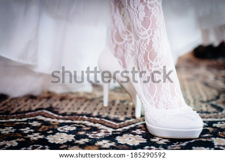 Bridal Shoes. beautiful bride in white wedding dress. Happy sexy girl waiting for groom. Romantic lady in bridal dress and flowers in hair have final preparation for wedding - stock photo