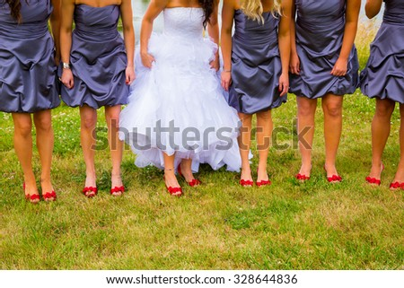 Bride and bridesmaids holding their dresses up a bit to show off their red shoes while standing on green grass. - stock photo
