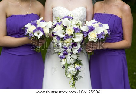 bride and bridesmaids with purple wedding bouquets - stock photo