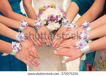 bride and bridesmaids with violet bracelets on hands - stock photo