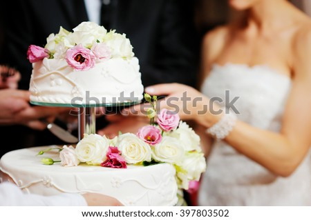 Bride and groom are cutting their wedding cake at wedding reception - stock photo