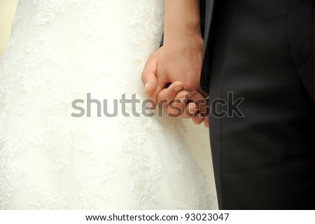 Bride and groom are holding each other's hands at wedding - stock photo