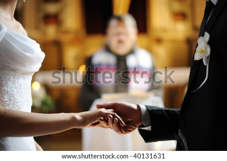 Bride and groom are holding each other's hands during church wedding ceremony - stock photo