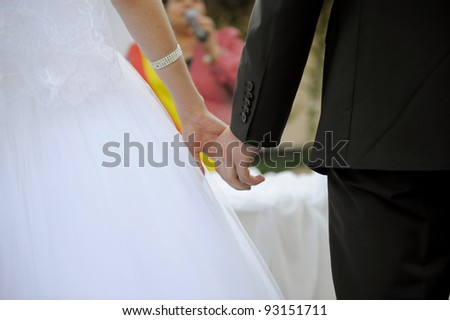 Bride and groom are holding each others hands at wedding - stock photo