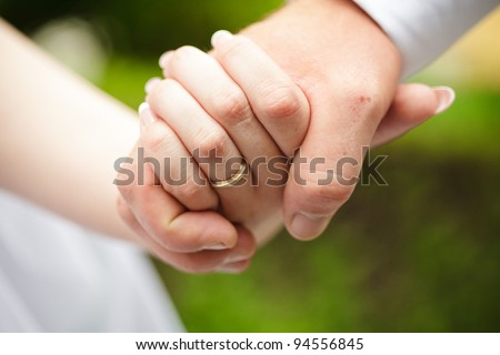 Bride and groom are holding hands each other - stock photo