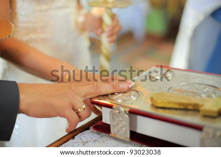 Bride and groom are holding hands on bible - stock photo