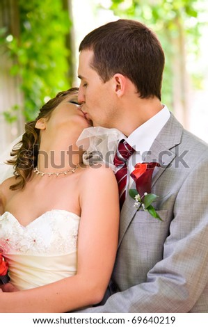 bride and groom are kissing at park