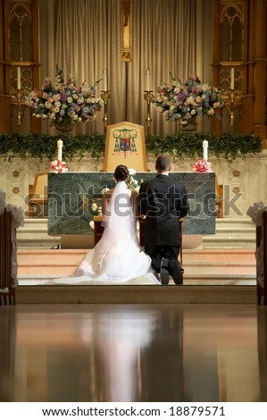 Bride and groom at church wedding alter ceremony - stock photo