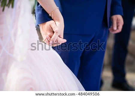 Bride and groom at the wedding ceremony holding hands, closeup