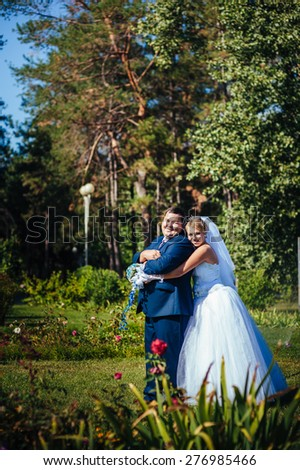 Bride and Groom at wedding Day walking Outdoors on spring nature. Bridal couple, Happy Newlywed woman and man embracing in green park. Loving wedding couple outdoor. - stock photo