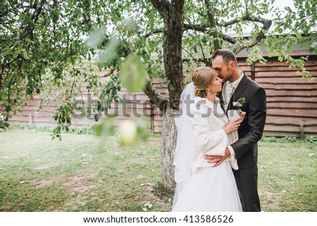 Bride and groom at wedding Day walking Outdoors on spring nature. Bridal couple, Happy Newlywed woman and man embracing in green park. Loving wedding couple outdoor. Bride and groom