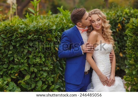 Bride and Groom at wedding Day walking Outdoors on summer green nature. Bridal couple, Happy Newlywed woman and man embracing and kissing in green park. Loving wedding couple outdoor. Bride and groom - stock photo