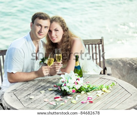 Bride and groom at wedding table near the sea