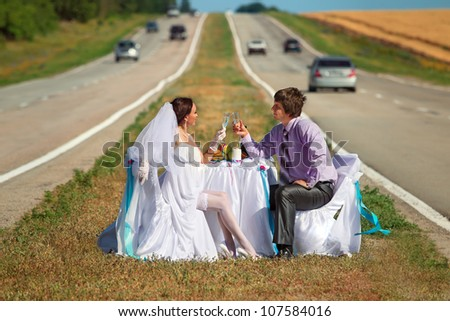 Bride and groom at wedding table on the countryside road - stock photo