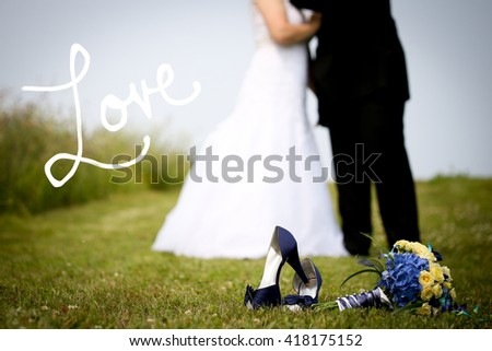 Bride and groom blurred in background. Shoes and flowers in focus with copy space on left. Love handwritten text on left in white. - stock photo