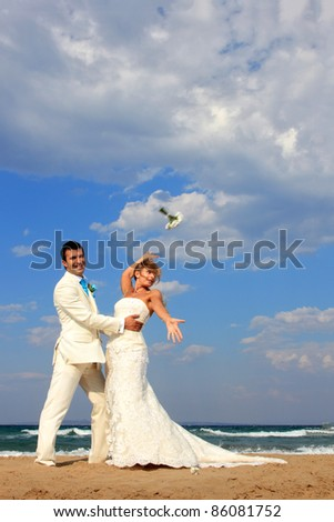 Bride and groom by the sea on their wedding day - the bride is throwing her bouquet - stock photo
