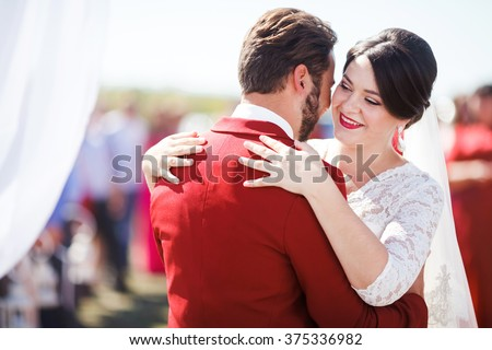 Bride and groom dancing at the wedding ceremony on the background of white cloth, outdoors. Marsala color and decoration style. - stock photo