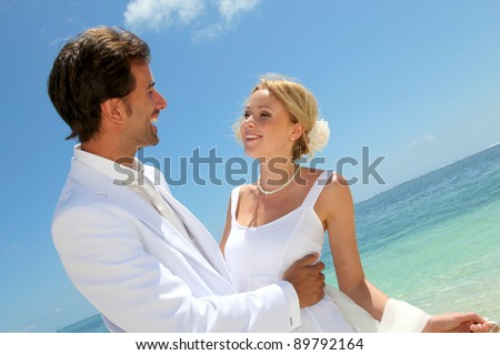 Bride and groom dancing by blue lagoon - stock photo