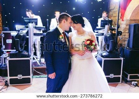 bride and groom dancing first dance indoor with colorful lights - stock photo