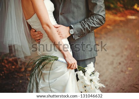 Bride and groom embrace each other - stock photo