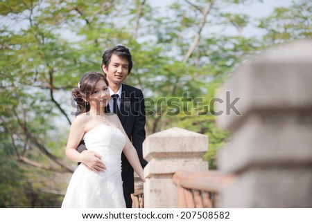 Bride and groom Embrace each other in the garden - stock photo