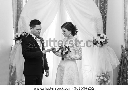 bride and groom exchange rings. The groom wears a wedding ring to the bride. Wedding ceremony. - stock photo