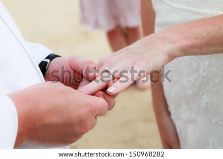 Bride and groom exchanging wedding rings. - stock photo