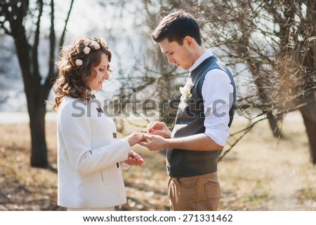 Bride and groom exchanging wedding rings. Wedding couple. People in love. Young man and beautiful woman in spring park. Marriage proposal. Outdoors wedding ceremony. Happy people - stock photo