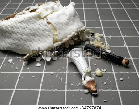 Bride and groom figurines lying at destroyed wedding cake on tiled floor - stock photo