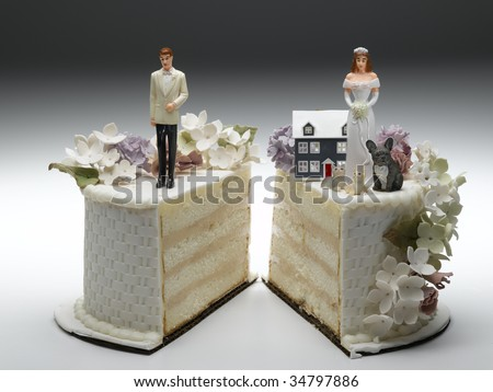 Bride and groom figurines standing on two separated slices of wedding cake - stock photo