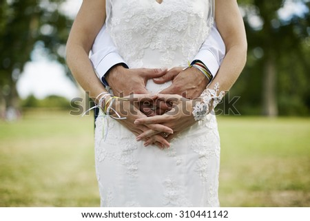 Bride and groom focus on Hands crossed over natural background - stock photo