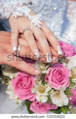 Bride and groom hand in hand with a ring