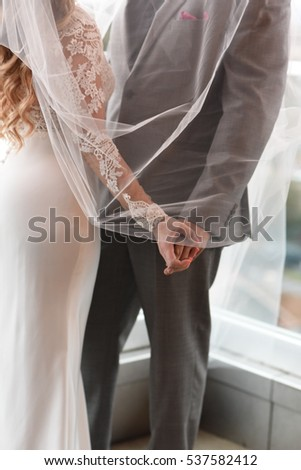 Bride and groom hands white dress and grey tux