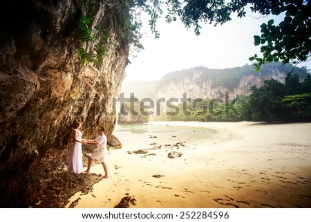 bride and groom hold together hand in hand on sand beach near cliff against sea rocks trees  - stock photo